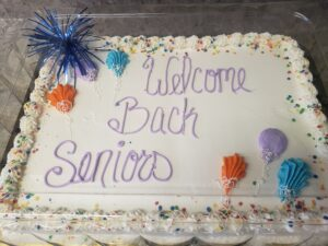 White frosted cake with Welcome Back Seniors written in purple frosting
